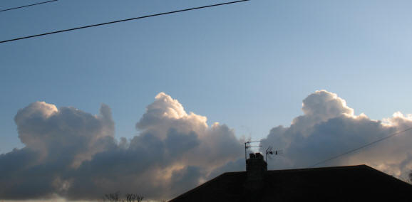 Three piles of cumulus clouds